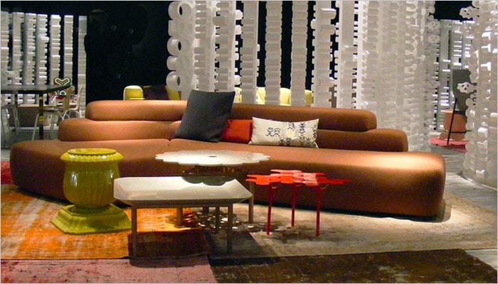Design woonkamer met oranje zetel en kleurrijk tafeltje