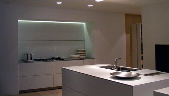 moderne keuken in corian met ingebouwde keukenkasten in nis en indirecte verlichting