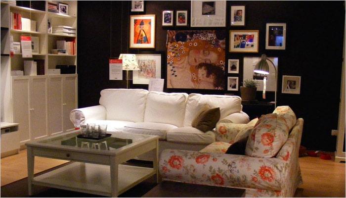 landelijke woonkamer met bloemenzetel en zwarte muur met fotokaders