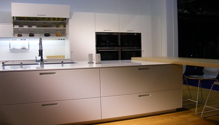 Open witte design keuken met grote schuiven en houten werkblad