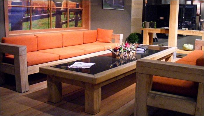 houten zetel en salontafel met opvallende oranje kussens in landelijke stijl